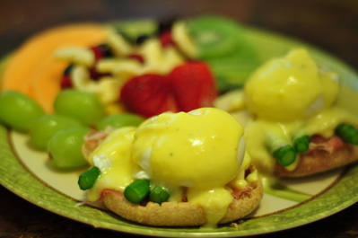 Eggs Benedict with fruit in the background