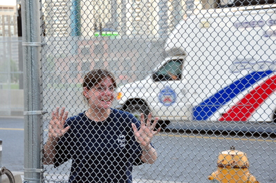 Kim with fence and Police truck